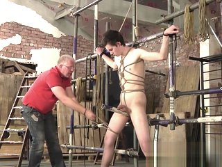 Mature master Sebastian Kane strokes his bound slaves cock